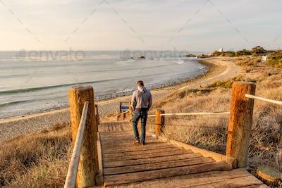 Man walking at boardwalk to beach, Malibu.
