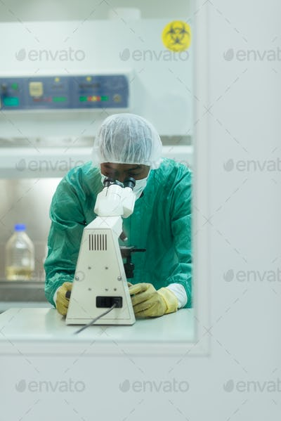 Man At Work With Microscope In Biotechnology Lab