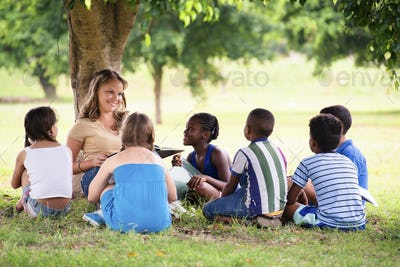 Children And Education Teacher Reading Book To Young Students