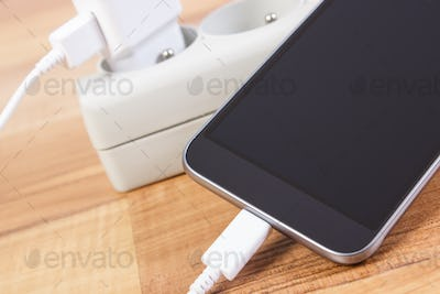 Smartphone with connected plug of charger, telephone charging