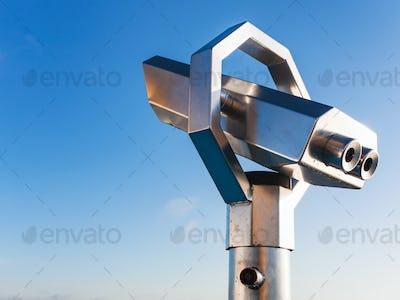 stationary observation binoculars and blue sky