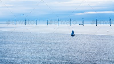 airplane, ships and bridge near offshore wind farm