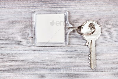 key with key chain on wooden board