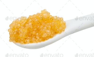 yellow caviar of pike fish in ceramic spoon