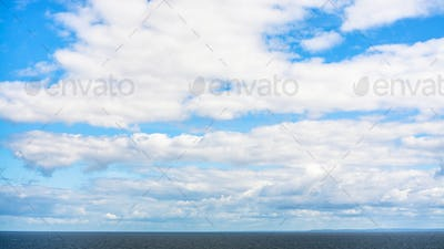 white clouds in blue sky over calm Baltic Sea