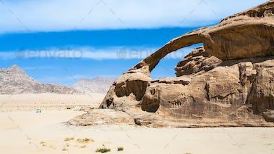 car near sandstone rock in Wadi Rum desert