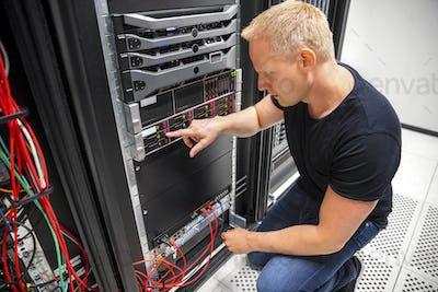 IT Technician Monitors Server On Rack In Datacenter