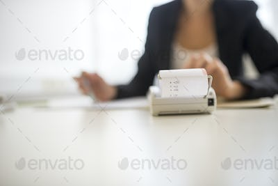 Adding machine in foreground with obscured worker