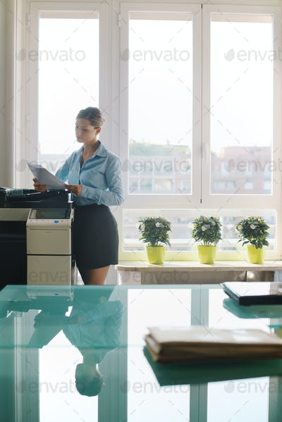 Young Woman Copying Document With Photocopy In Office