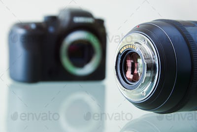 Closeup Of DSLR Photo Camera And Still Lens On Desk