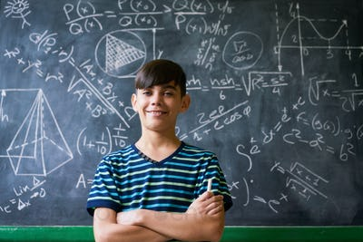 Confident Latino Boy Smiling At Camera During Math Lesson