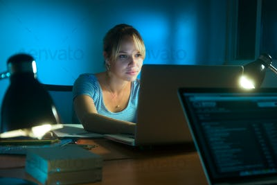 Woman Writing On Laptop Computer Late At Night