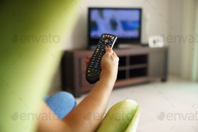 Woman On Sofa Watching Tv Changing Channel With Remote