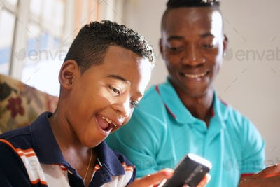 Father Teaching Mobile Telephone Technology To Son At Home