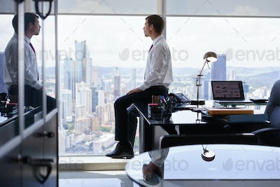 Business Person Sits On Desk Looking Out Of Office Window