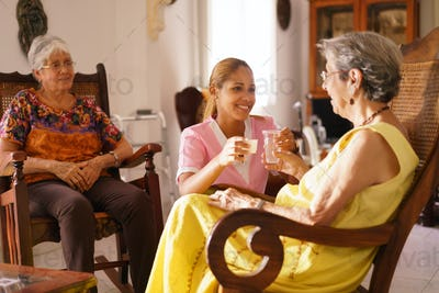 Hospice Nurse Serving Pill Medicine Water To Old Woman