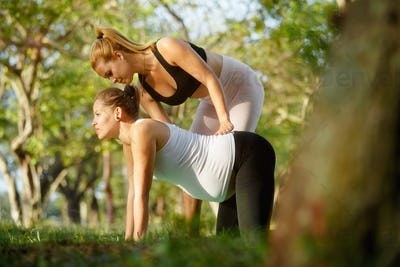 Yoga Trainer Helping Pregnant Woman With Exercise For Backpain