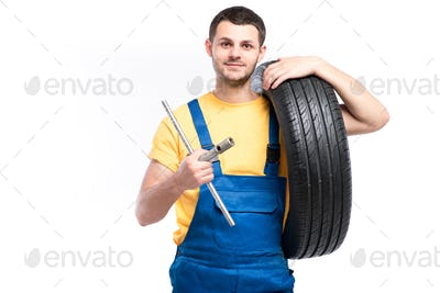 Service worker in blue uniform holds tire in hand