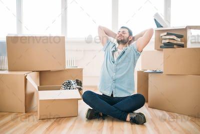 Thoughtful man sitting in yoga pose, housewarming