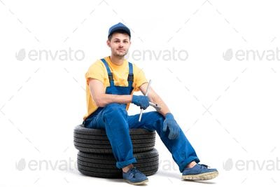 Car tire service, worker sitting on car tyres