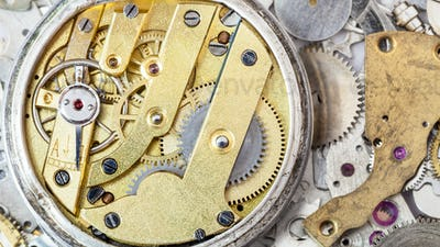 brass mechanical watch on heap of spare parts