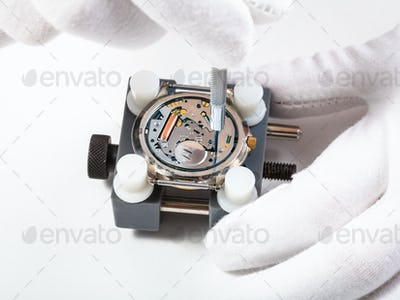 repairing quartz watch close up with screwdriver