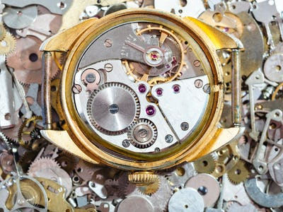 old golden watch on heap of clock spare parts