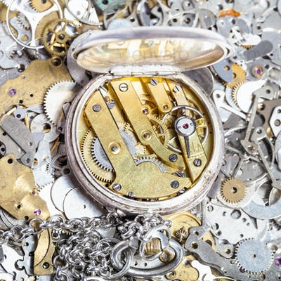 open retro pocket watch on heap of spare parts