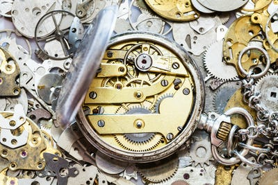 open vintage pocket watch on heap of spare parts