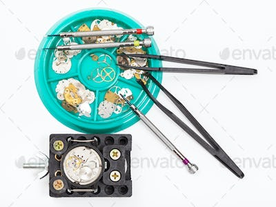 top view of tools and parts for repairing watch