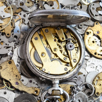 open vintage pocket watch on pile of spare parts