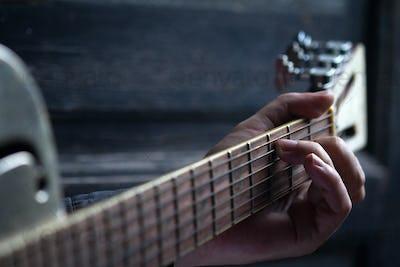 fingers on guitar dark background
