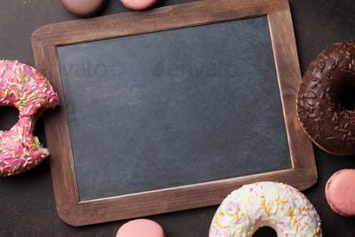 Chalkboard and colorful donuts on stone table