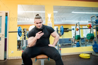 Handsome guy text messaging on his smartphone at gym.