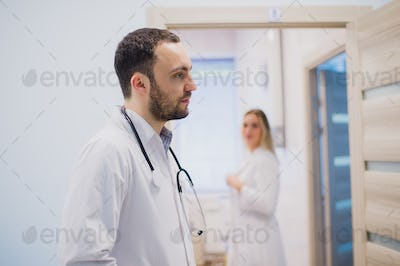 pensive young doctor in white coat holding diagnosis in hospital, caring doctor concept