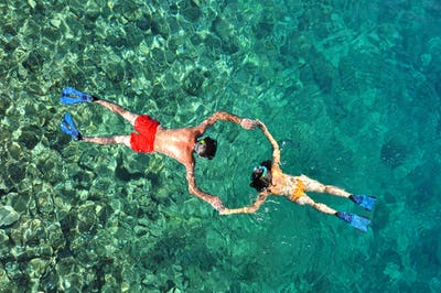 Young couple snorkeling in clear tropical water over coral reef. Above view