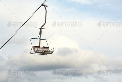 Empty chairlift with cloudy sky in the background