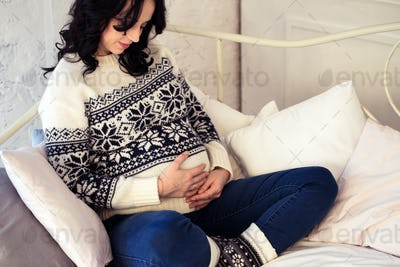 Pregnant woman resting on sofa in the room