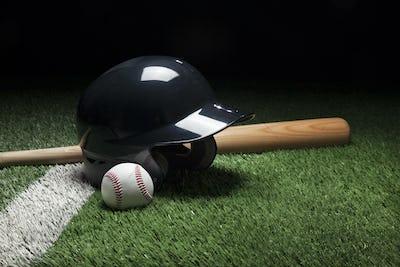 Baseball Helmet Ball and Bat on Green Field with Dark Background