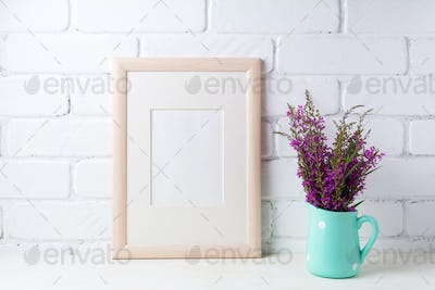Wooden frame mockup with maroon purple flowers in mint pitcher
