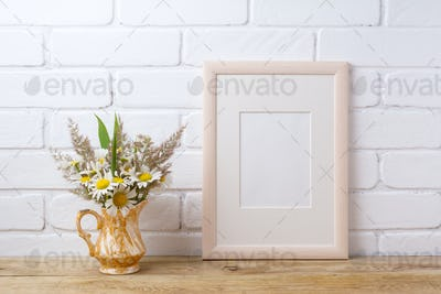 Wooden frame mockup with chamomile and grass in golden pitcher