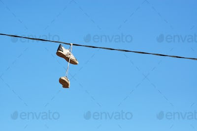 Pair of old shoes hanging on power line.