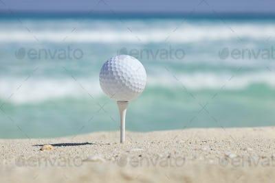 Golf Ball on a Tee in Sand on a Tropical Beach