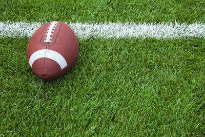 Football on Grass Field with White Stripe