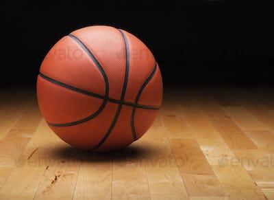 Basketball on a Maple Hardwood Court Floor with Dark Background
