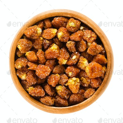 Physalis fruits, dried, in wooden bowl over white