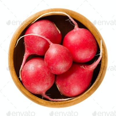 Red radishes in wooden bowl over white