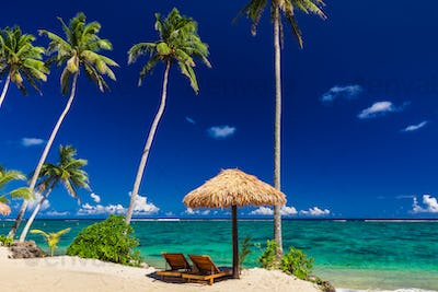 Two beach chair under umbrella with palm trees, Samoa