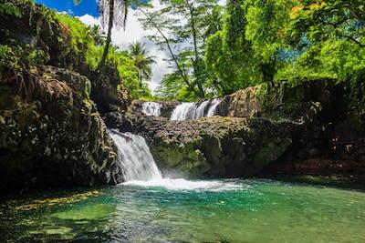 Vibrant Togitogiga falls with swimming hole on Upolu, Samoa