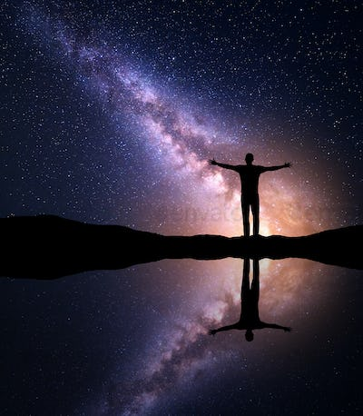 Milky Way and silhouette of a man near the lake